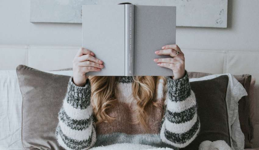 mulher lendo livro na cama debaixo das cobertas