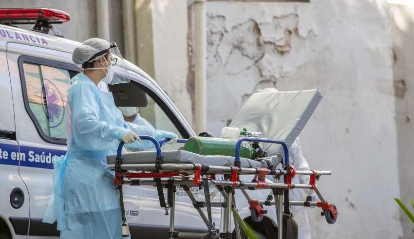 Funcionário da Saúde leva maca com oxigênio para atendimento de paciente
