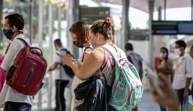 pessoas usando máscara esperando o ônibus
