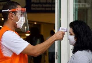 Funcionário medindo temperatura em frente ao Shopping Cidade em BH